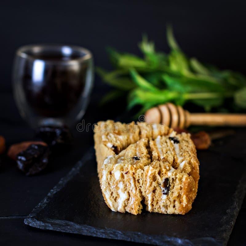 Zoete eigengemaakte gelaagde honingscake op een zwarte lijst met kruiden en noten royalty-vrije stock foto