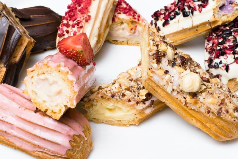 Zoete en kleurrijke Franse eclairs met berrys, chocolade, noten Groep Frans dessert Eclair achtergrond Heerlijke kleurrijke ecl stock foto
