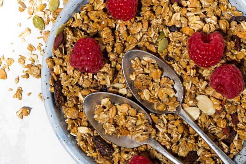 zoete granola op de plaat en verse frambozen op witte lijst royalty-vrije stock afbeeldingen