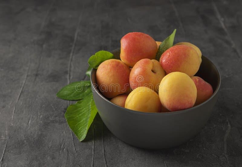Zoete heerlijke abrikoos op donker de zomer vers fruit van de kom grijs lijst stock afbeelding