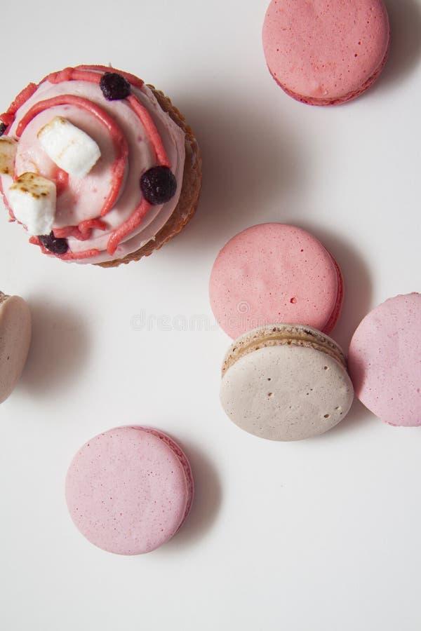 Zoete heerlijke cupcakes en roze macarons op wit stock afbeeldingen