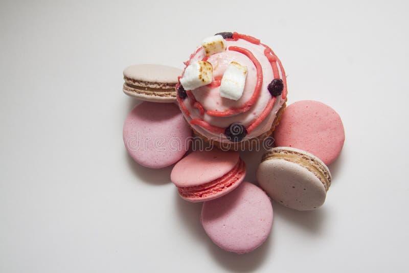 Zoete heerlijke cupcakes en roze macarons op wit stock afbeelding