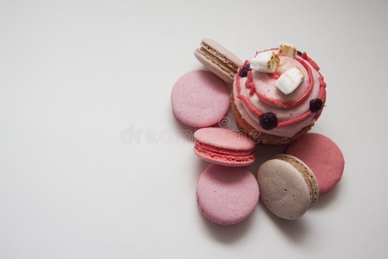 Zoete heerlijke cupcakes en roze macarons op wit royalty-vrije stock foto's