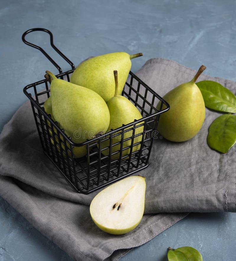 Zoete heerlijke groene peren binnen zwarte mand op het blauwe lijstfruit royalty-vrije stock afbeelding