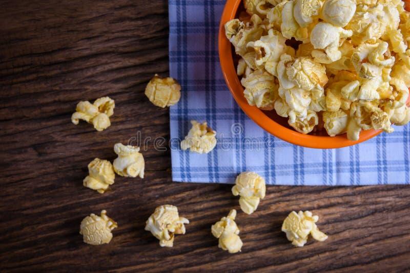 Zoete karamelpopcorn in een kom op blauw katoenen servet tegen wo royalty-vrije stock foto's