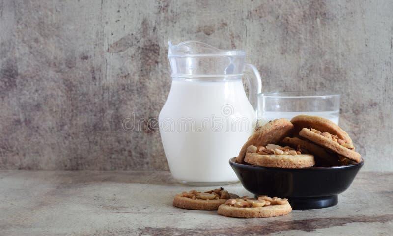 Zoete koekjes met geroosterde pinda's op een mooie plaat en op de lijst Kruik vers melk en glas op grijze achtergrond stock foto's