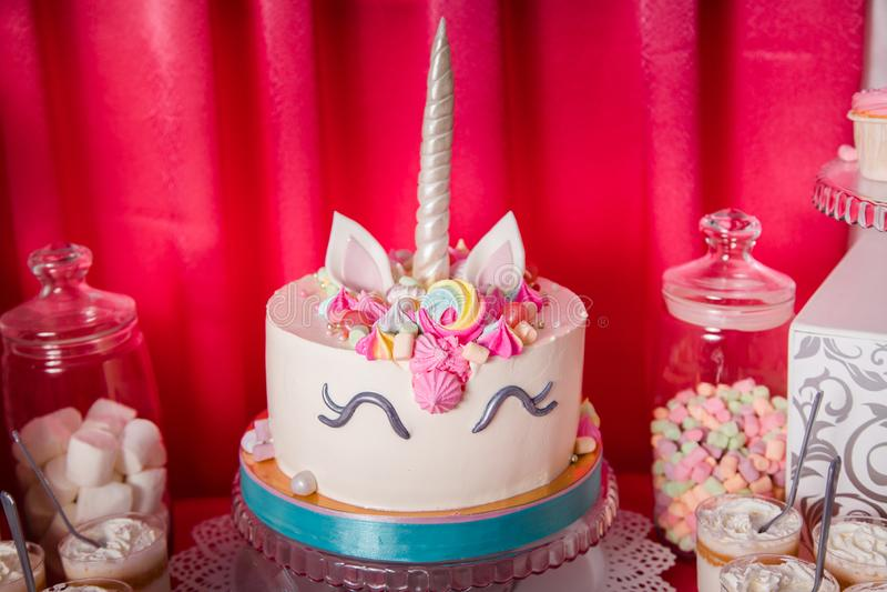 Zoete lijst en grote eenhoorncake voor de eerste verjaardag van het babymeisje Suikergoedbar met heel wat verschillend suikergoed royalty-vrije stock foto