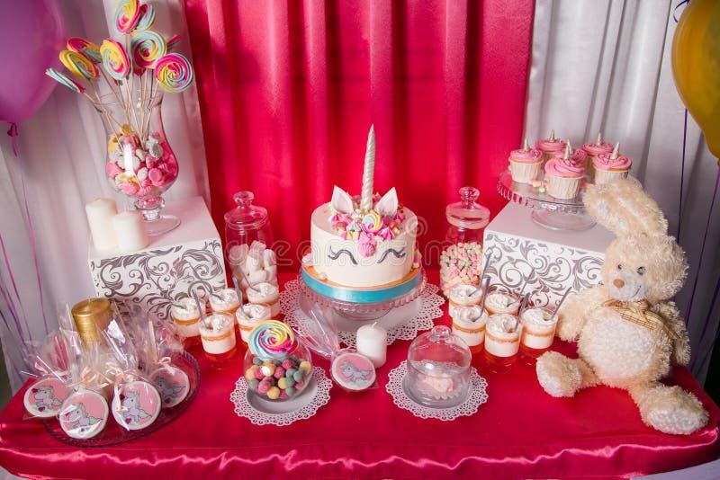 Zoete lijst en grote eenhoorncake voor de eerste verjaardag van het babymeisje Suikergoedbar met heel wat verschillend suikergoed royalty-vrije stock foto's
