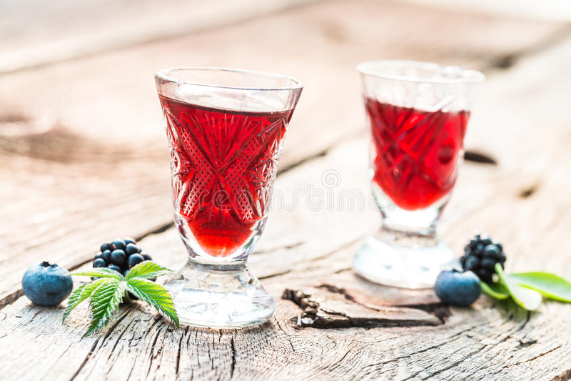 Zoete likeur met alcohol en bessen in de zomer stock foto
