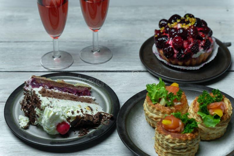 Zoete maaltijd voor twee: rode wijn, pastei met suikerglazuur en fruit, Franse pasteitjes en schococake royalty-vrije stock foto's