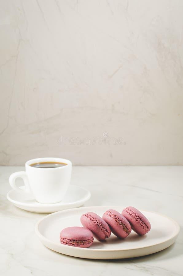 Zoete makarons of macaron in een witte kom en koffiekop op een witte achtergrond, Frans dessert stock fotografie