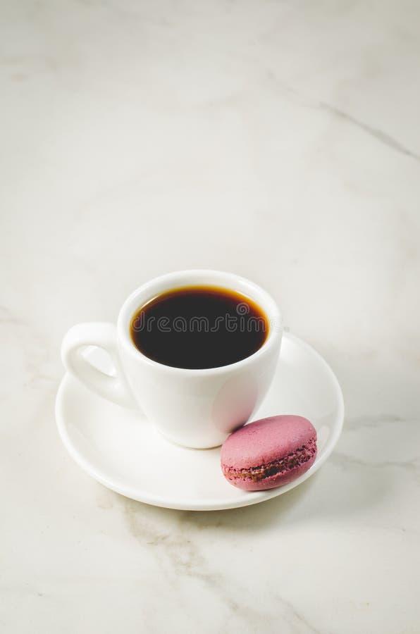 Zoete makarons of macaron en koffiekop op een witte achtergrond, Frans dessert stock foto