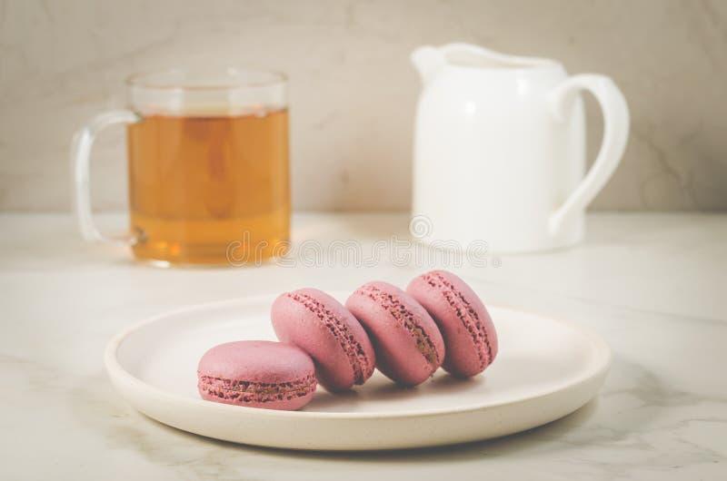 Zoete makarons of macaron en thee in een glas op een witte achtergrond, Frans dessert royalty-vrije stock foto's