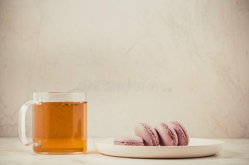 Zoete makarons of macaron en thee in een glas op een witte achtergrond, Frans dessert royalty-vrije stock foto