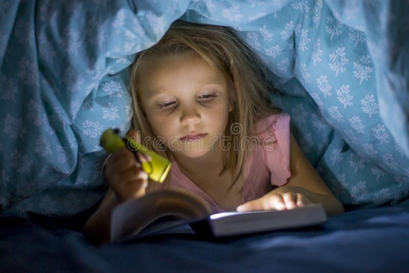 Zoete mooi en mooi weinig blond meisje 6 tot 8 jaar oud onderbed behandelt lezingsboek in dark bij nacht met toortslicht royalty-vrije stock fotografie
