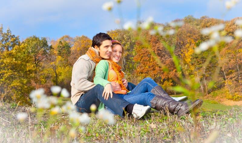 Zoete paarzitting op een heuvel bij het de herfstlandschap stock afbeeldingen