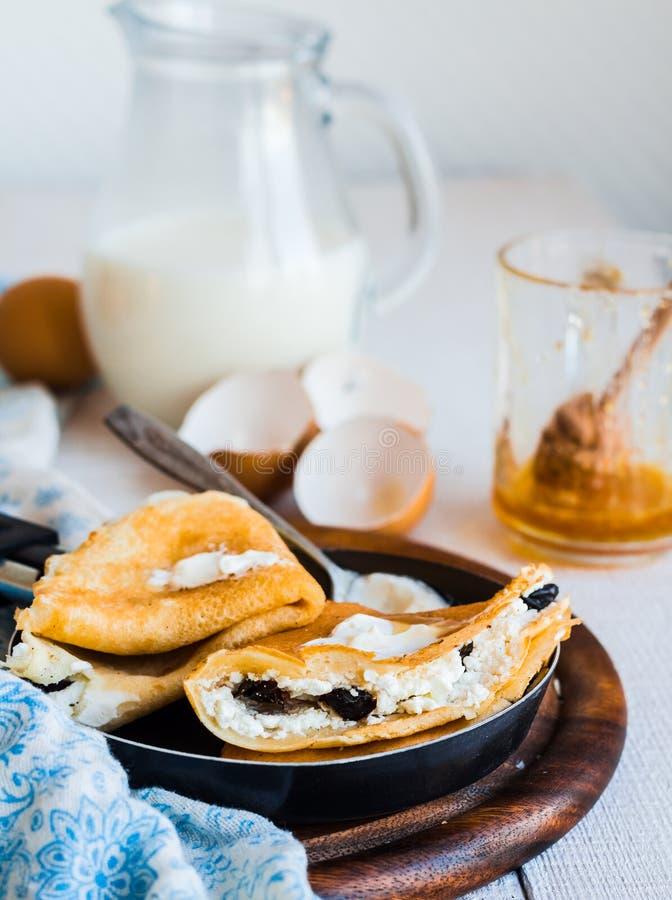 Zoete pannekoeken met kwark, gedroogde pruimen, honing in het braden p stock afbeelding