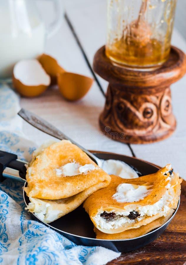 Zoete pannekoeken met kwark, gedroogde pruimen, honing in het braden p stock foto