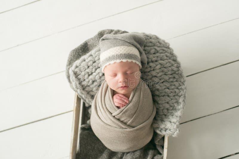 Zoete pasgeboren babyslaap in een mand Mooie pasgeboren jongen stock afbeelding