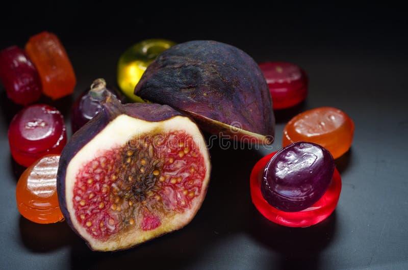 Zoete, rijpe fig. op een achtergrond van kleurrijk suikergoed Multicolored achtergrond, screensaver royalty-vrije stock foto
