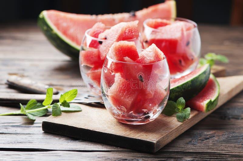 Zoete rode watermeloen en munt op de houten lijst royalty-vrije stock foto