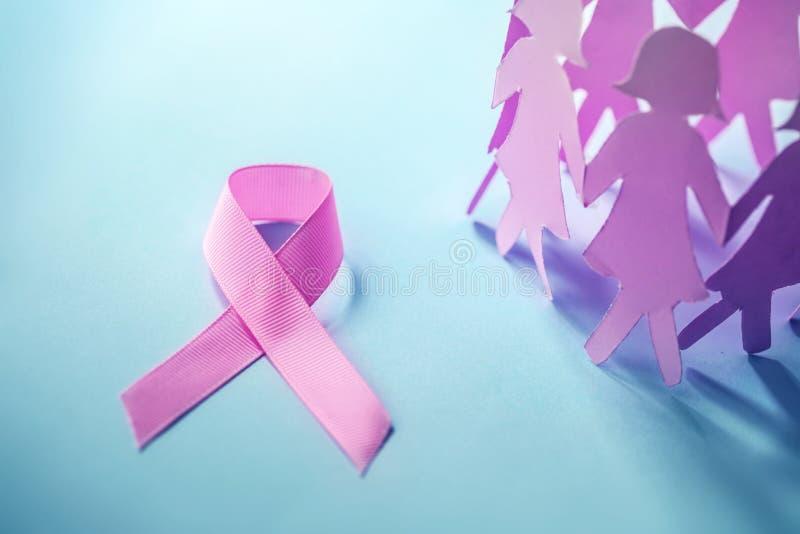 Zoete roze lintvorm met de meisjesdocument pop op blauwe backgro stock foto
