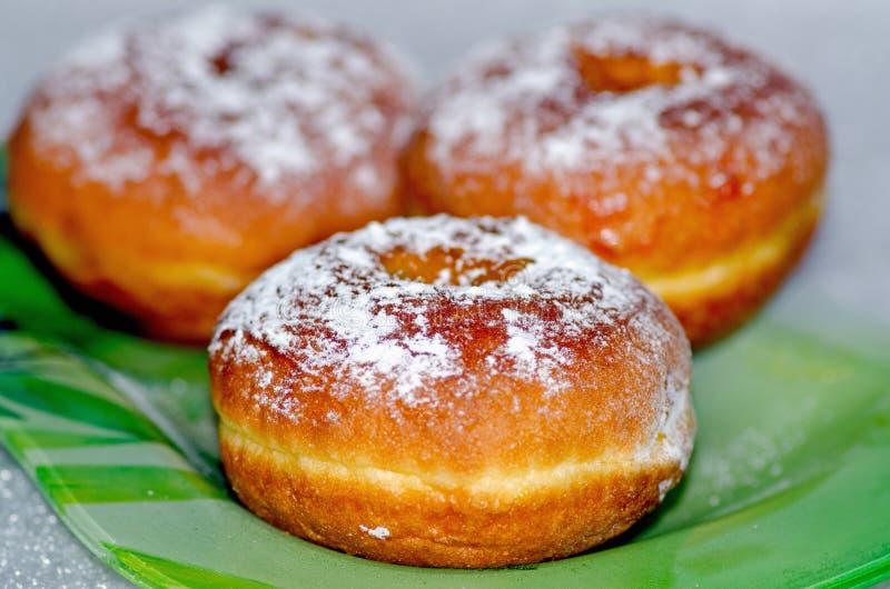 Zoete smakelijke die donuts met gepoederde suiker wordt bestrooid liggen op een groene glasplaat, de nationale schotel voor de va royalty-vrije stock foto