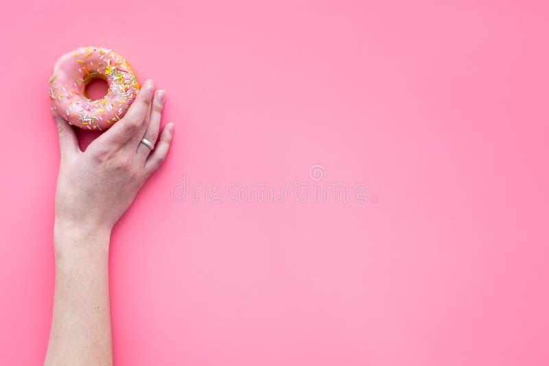 Zoete smakelijke snack Handgreep verglaasde doughnut op de roze ruimte van het achtergrond hoogste meningsexemplaar royalty-vrije stock afbeelding