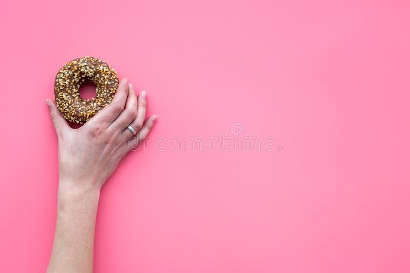 Zoete smakelijke snack Handgreep verglaasde doughnut op de roze ruimte van het achtergrond hoogste meningsexemplaar royalty-vrije stock foto's