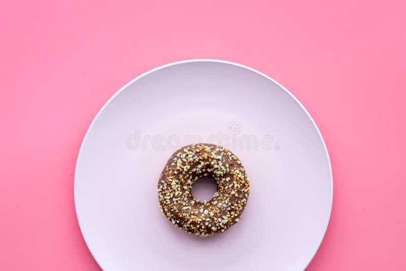 Zoete smakelijke snack Verglaasde doughnut op plaat op de roze ruimte van het achtergrond hoogste meningsexemplaar stock afbeelding