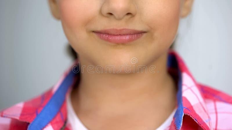 Zoete tiener die bij camera, tedere kindlippen en huidzorg glimlachen, schoonheidsmiddelen stock foto's
