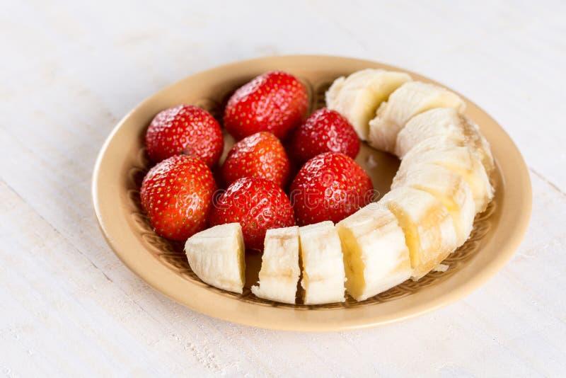 Zoete verse aardbeien met gesneden banaan op de plaat royalty-vrije stock foto