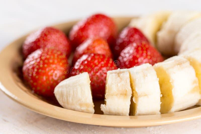 Zoete verse aardbeien met gesneden banaan op de plaat stock foto