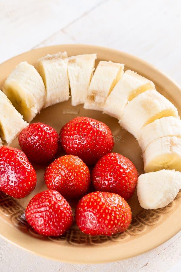 Zoete verse aardbeien met gesneden banaan op de plaat royalty-vrije stock fotografie