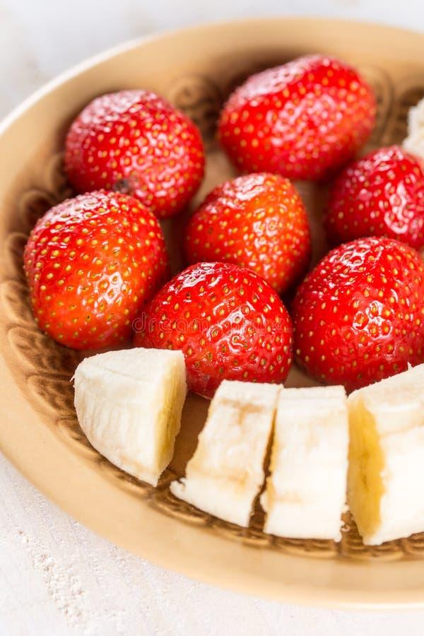 Zoete verse aardbeien met gesneden banaan op de plaat stock afbeelding
