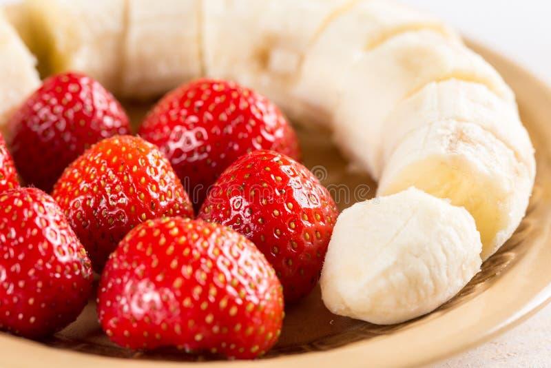 Zoete verse aardbeien met gesneden banaan op de plaat stock fotografie