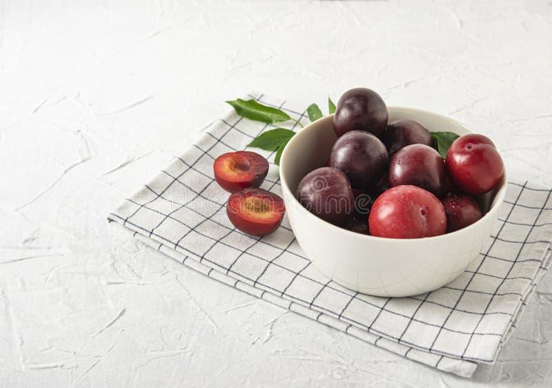 Zoete verse heerlijke rode pruimen op de witte kom en handdoek witte houten vruchten van de lijstzomer stock fotografie