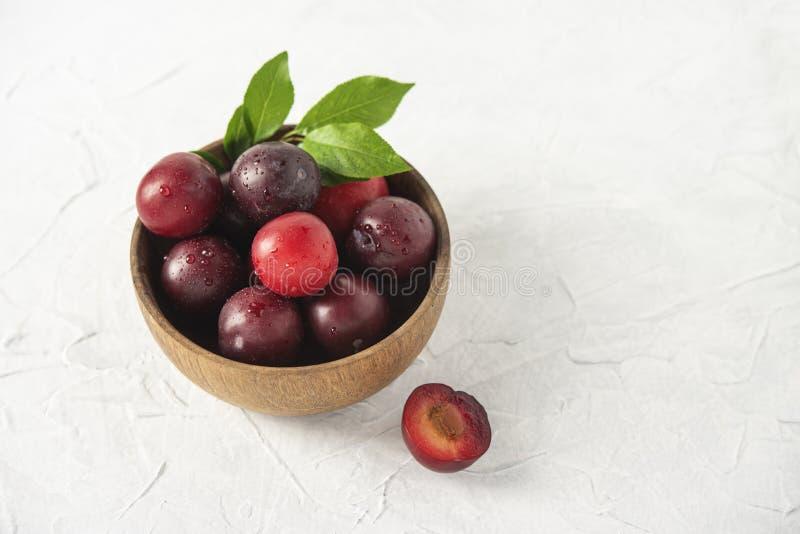 Zoete verse heerlijke rode pruimen op de zomervruchten van de kom witte houten lijst stock foto