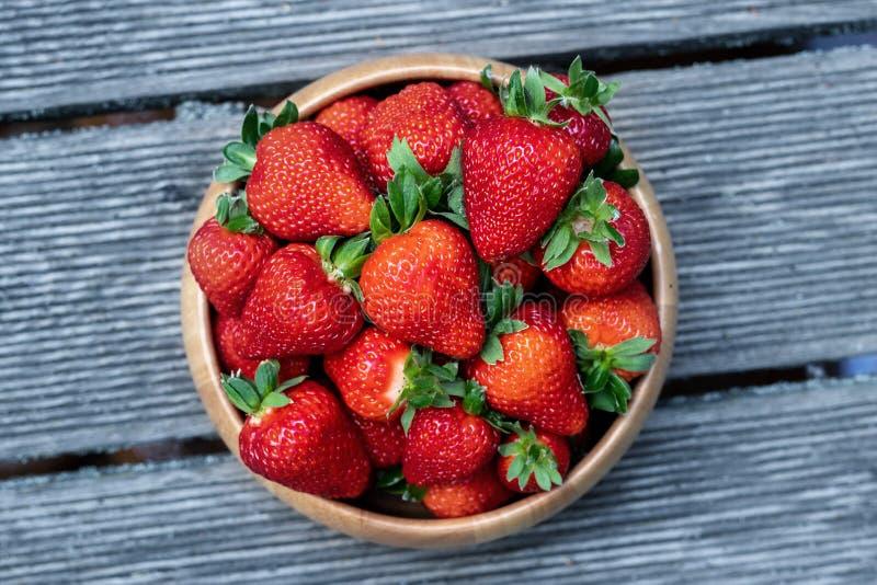 Zoete verse sappige organische rijpe aardbeien in houten kom op houten oppervlakte in openlucht stock foto