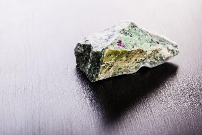 Zoisite stone on wood stock photo