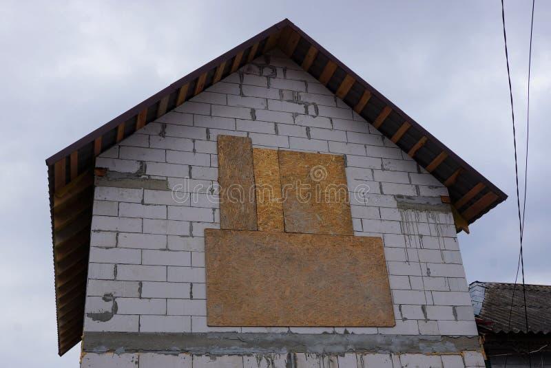 Zolder van een grijs baksteenhuis met ingescheept op venster royalty-vrije stock afbeelding