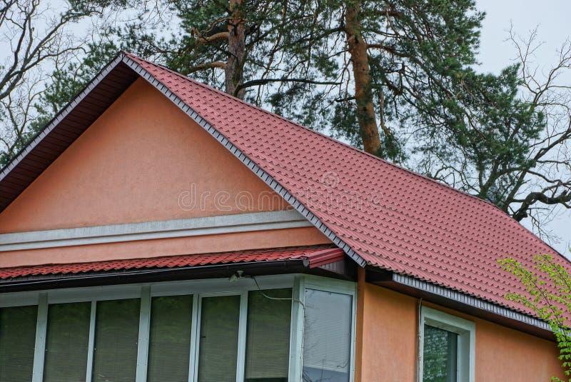 Zolder van een huis met vensters en een dak onder de rode tegels royalty-vrije stock afbeelding