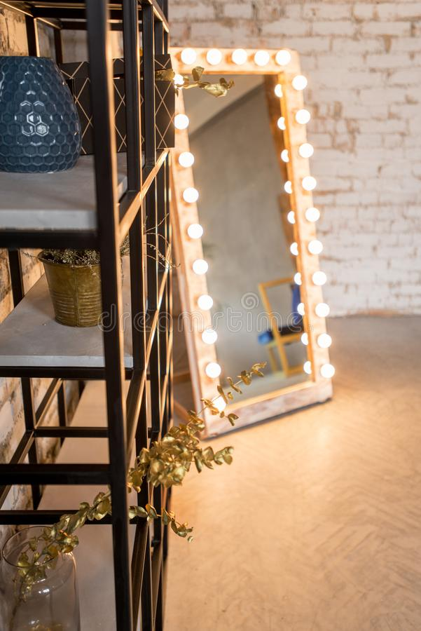 Zolderbinnenland met spiegel, bakstenen muur, de woonkamer van de metaaldraaibank in modern ontwerp stock afbeelding