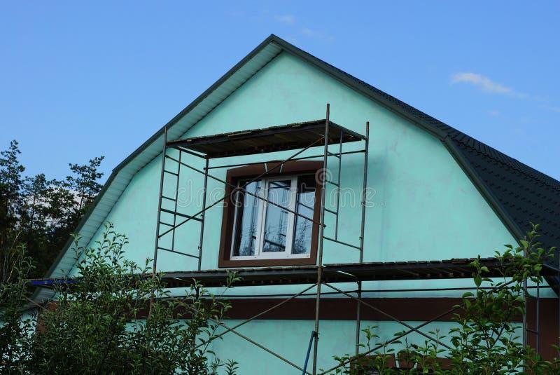 Zolderreparatie met een venster op de groene voorgevel stock afbeeldingen