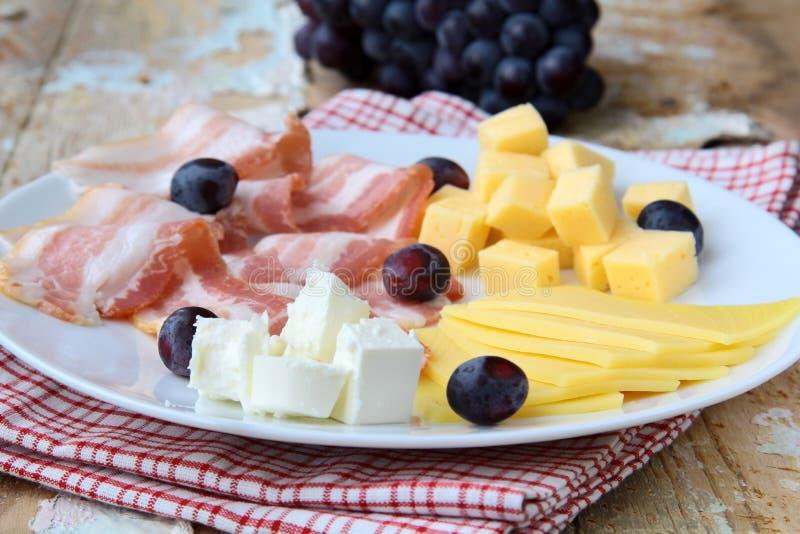 Zolla di formaggio con l'uva e la pancetta affumicata affumicata fotografia stock libera da diritti