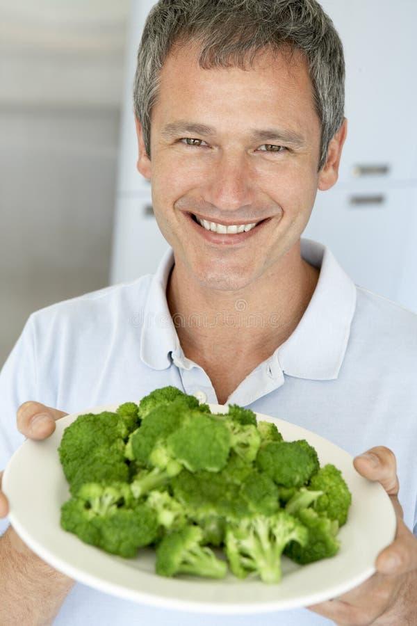 zolla invecchiata della metà dell'uomo della holding del broccolo immagini stock