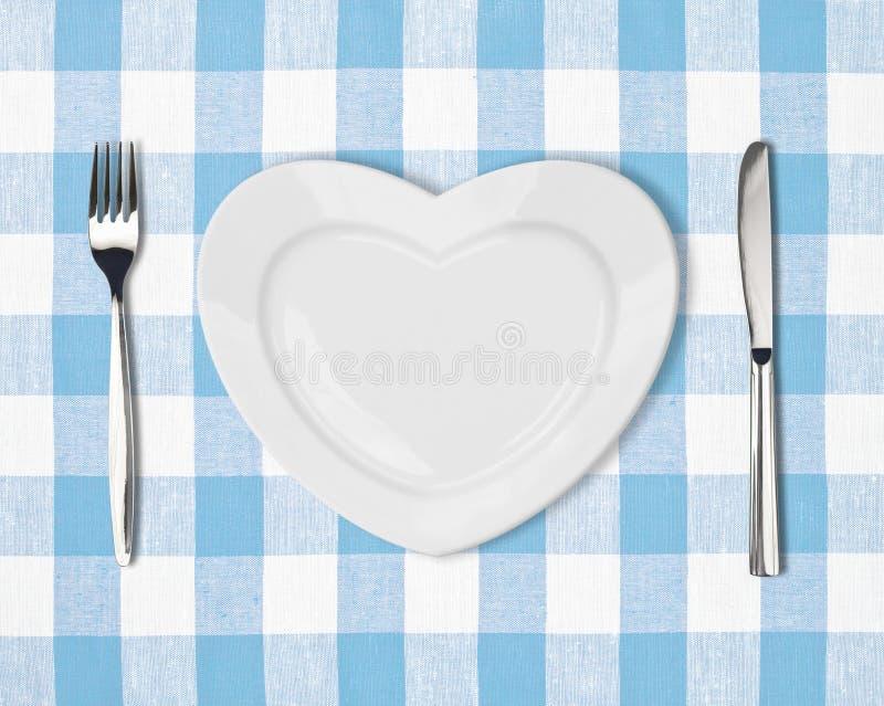 Zolla nella forma di cuore, del coltello di tabella e della forcella sulla tovaglia blu
