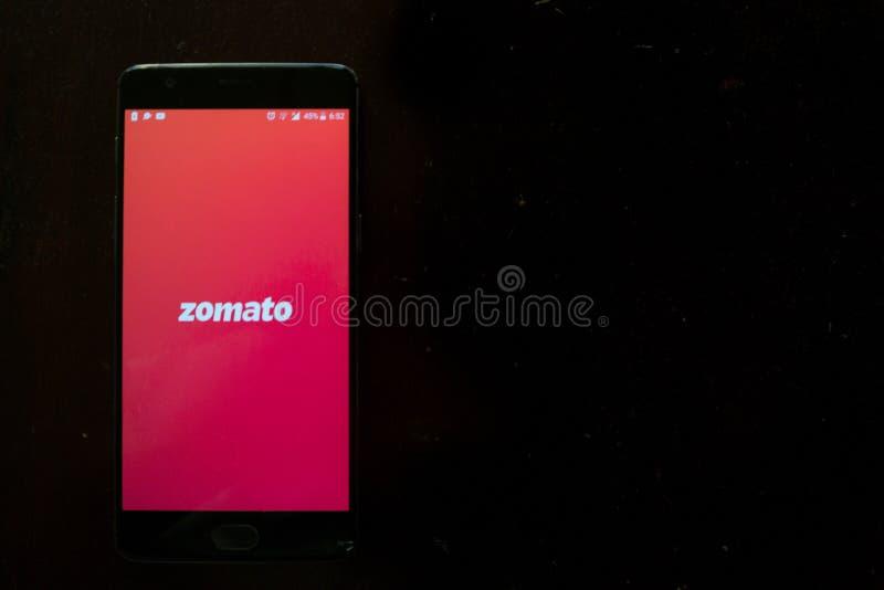 Zomato app exhibió un teléfono negro en una textura oscura - entrega app de la comida imagenes de archivo
