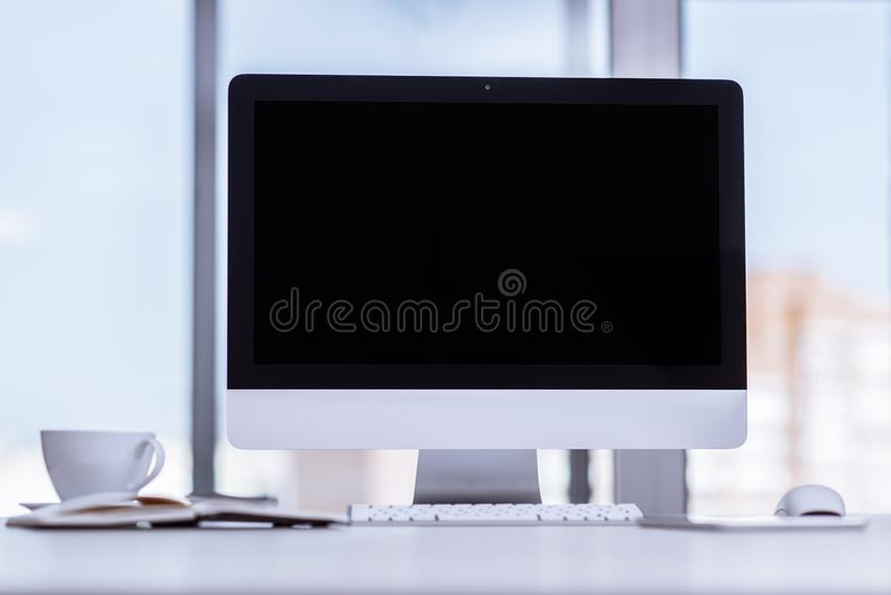 Zombaria acima da tela de computador de secretária preta na mesa no fundo do negócio do escritório fotografia de stock