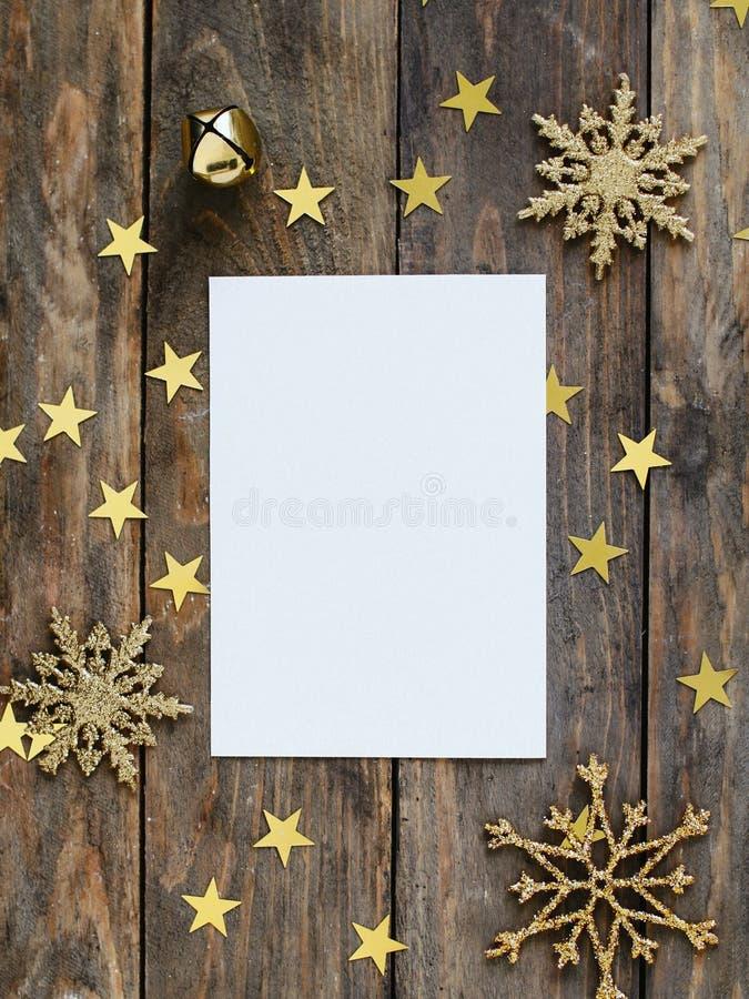A zombaria acima do cartão do greeteng no fundo rústico de madeira com os flocos de neve, o sino e o ouro do brilho das decoraçõe foto de stock royalty free